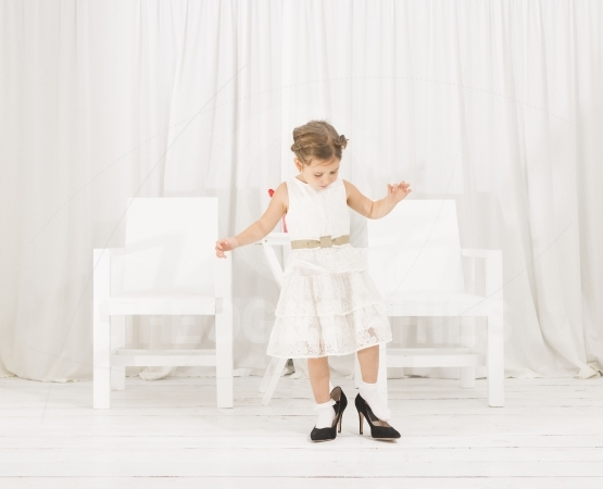 Little girl fashionista in her mother's big heeled shoes