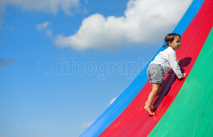 Little girl goes up on rainbow, at playground