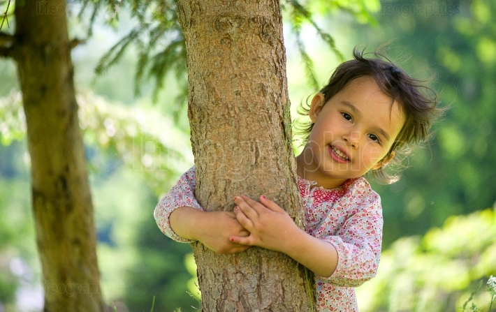 Little girl hugging the tree