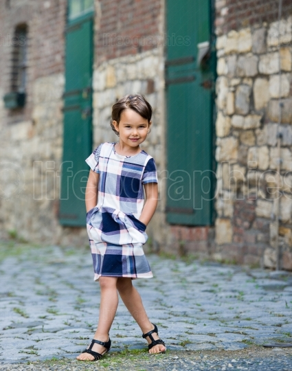 Little girl in an urban setting smiles at the camera