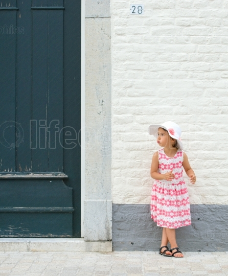 Little girl in pink dress and white summer hat outdoor