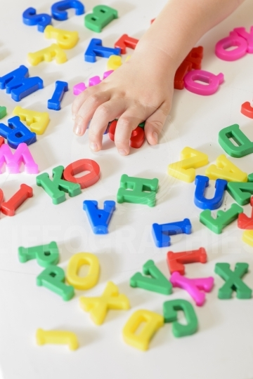 Little girl learning to read using magnetic letters