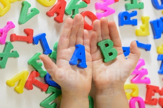 Little girl learning to read using magnetic letters holding in hands A and B
