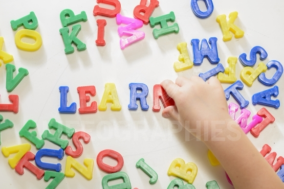 Little girl learning to write using magnetic letters