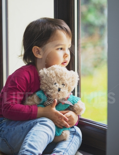 Little girl looking through window