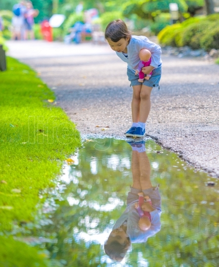 Little girl looks in a puddle like in a mirror