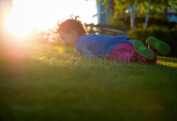 Little girl play on playground with white blur park background at sunset