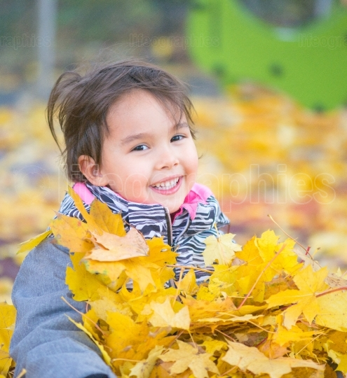 Little girl playing with leaves and smilling