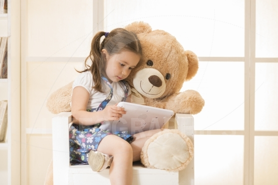 Little girl playing with teddy bear using tablet computer