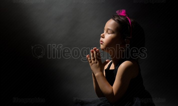 Little girl praying, isolated black background