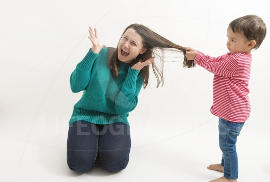 Little girl pulls her older sister hair