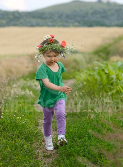 Little girl running in the wheat field