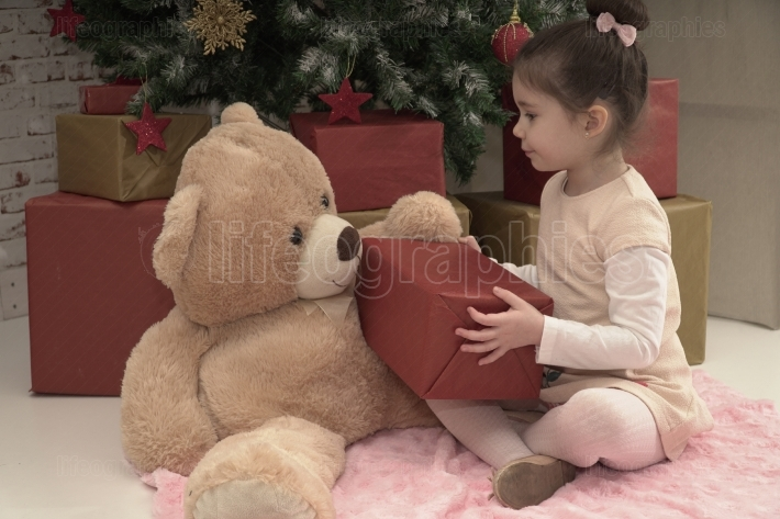 Little girl sharing presents with her toy bear friend on Christmas Eve