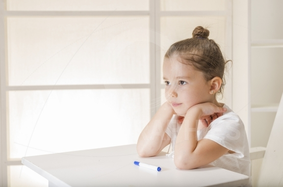 Little girl sitting at the desk waiting