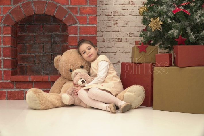 Little girl sitting on the floor with two different sizes toy bears waiting for Santa on Christmas Eve