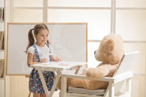 Little girl teaching her Teddy bear friend alphabet