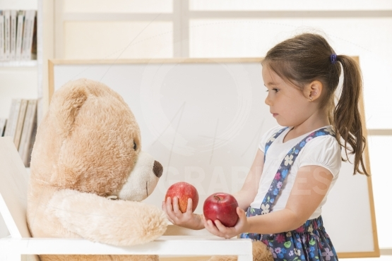 Little girl teaching her toy bear friend to count with apples, indoor shot