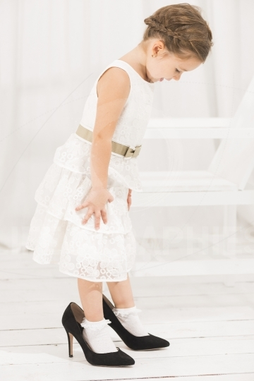 Little girl trying to walk with big high heel shoes