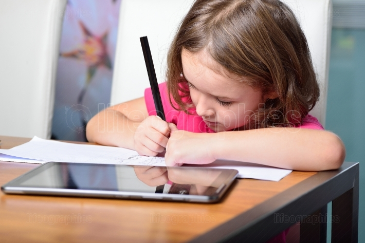 Little girl using a Tablet PC for homework.