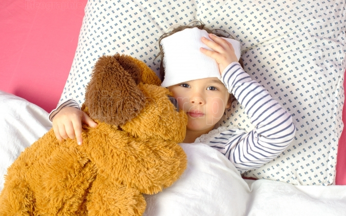 Little girl with a headache in bed with teddy bear