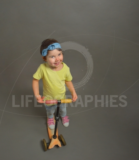 Little girl with a scooter isolated over grey