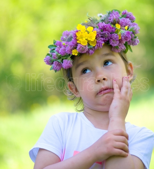 Little girl with a wreath of flowers on her head making a silly face