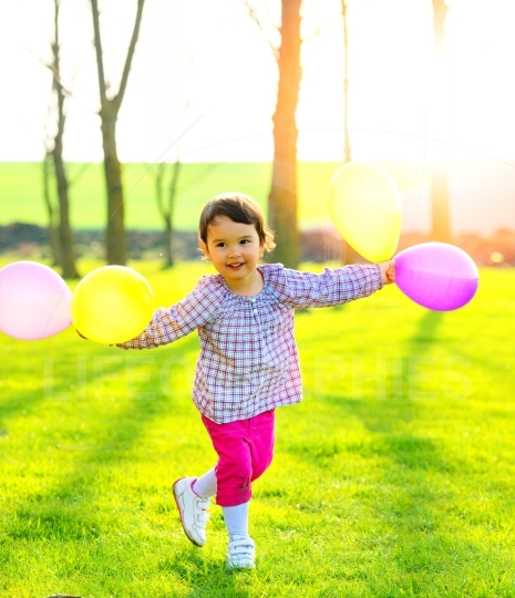 Little girl with balloons outdoors, dancing and enjoying nature