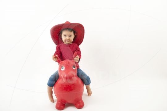 Little girl with red cowboy hat riding o toy horse isolated