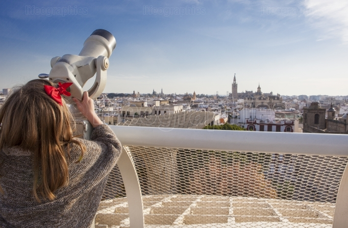 Little girl with telescope pointing to old town landmarks over M