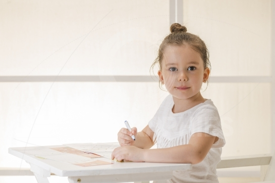 Little girl writing alphabet in a copy book at a desk