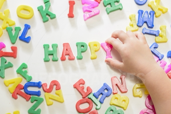 "Little girl writing ""happy"" using magnetic letters"
