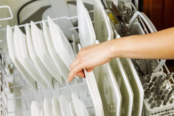 Loading dinner plates into the lower dish rack of dishwasher