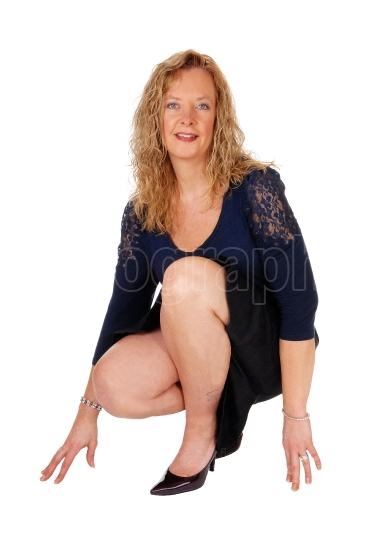 Lovely woman crouching on floor.
