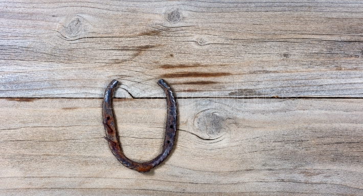 Lucky rusty horseshoe for St Patick holiday on wooden background