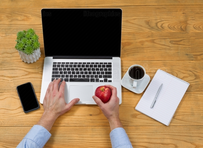 Male hand holding apple while using laptop computer
