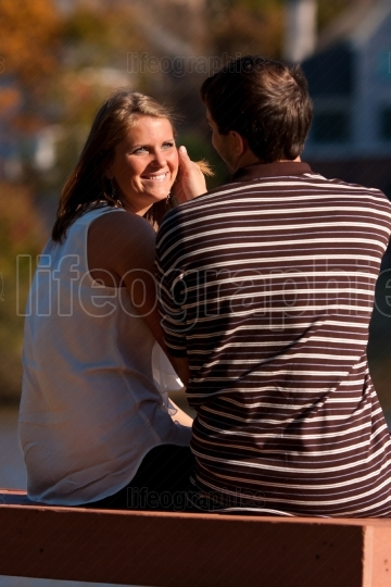 Man Caresses Sunlit Face Of Girlfriend Sitting On Bench