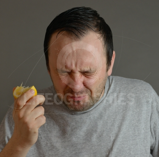 Man eating lemon and making silly faces