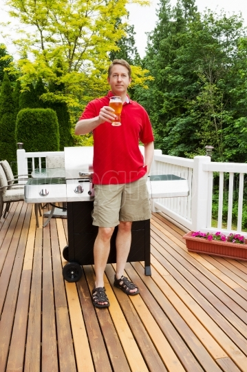 Man enjoying cold beer while preparing to cook outdoors