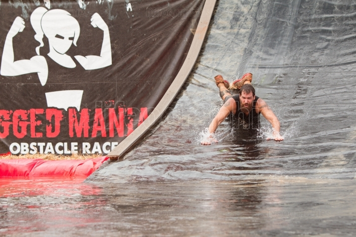 Man goes headfirst down water slide in obstacle course race
