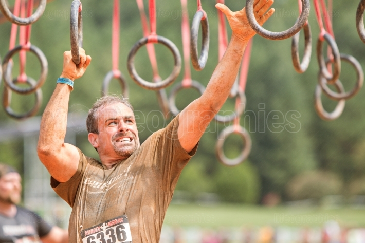 Man grabs onto suspended rings at extreme obstacle course race