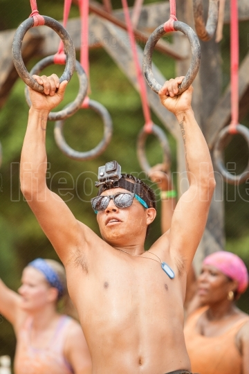 Man holds onto suspended rings at extreme obstacle course race