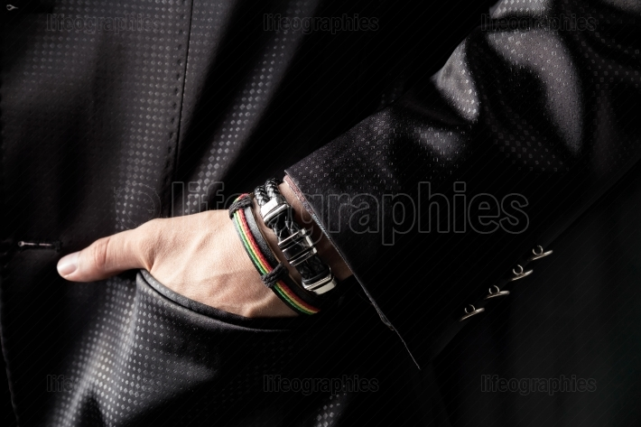Man in black costume and with colorful bracelets on hand