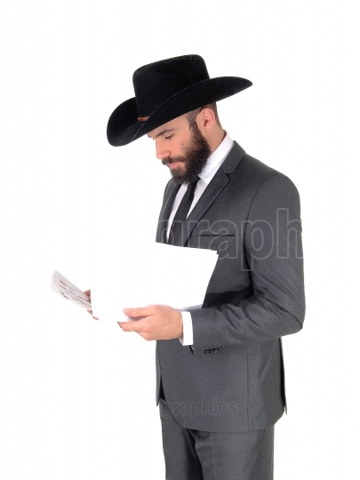 Man in suit and hat reading papers