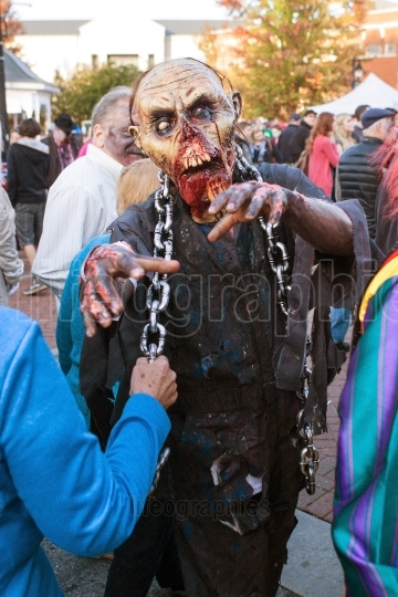 Man in terrifying zombie mask menaces people at halloween festiv