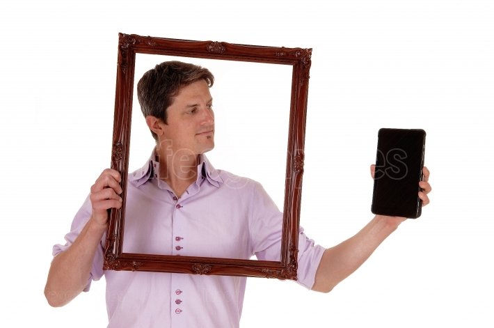 Man looking trough picture frame.