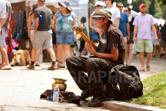 Man plays bass guitar for tips at arts festival