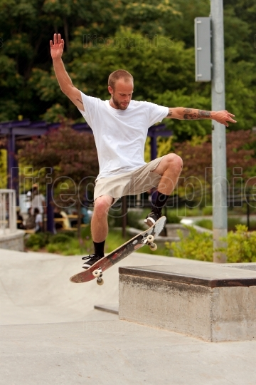 Man Practices Skateboard Trick At Park