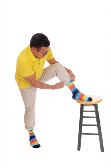 Man putting on his colorful socks.