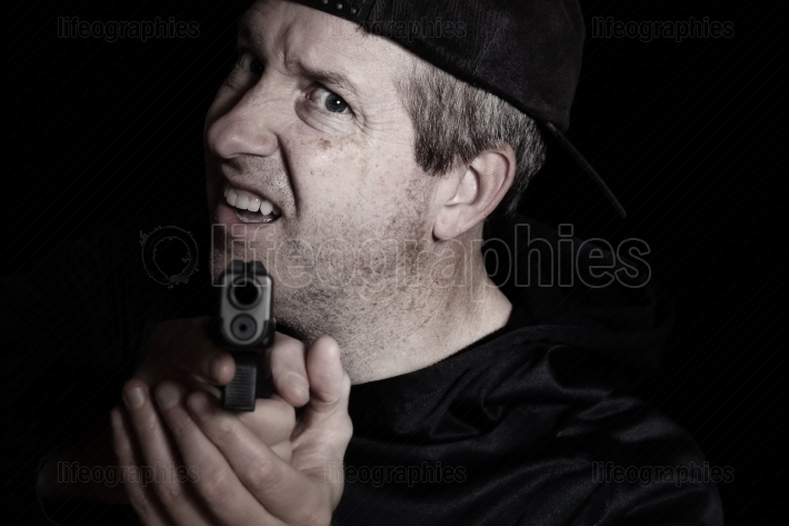 Man showing anger with weapon pointing forward in the dark