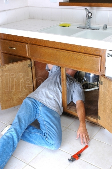 Man Under Sink Reaching for Wrench